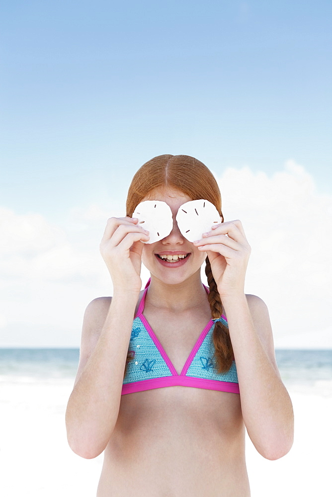 Girl on beach holding sand dollars over eyes