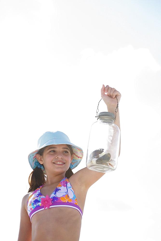 Girl at beach displaying jar of shells