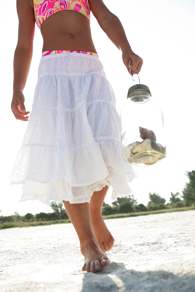 Girl on beach carrying jar of shells