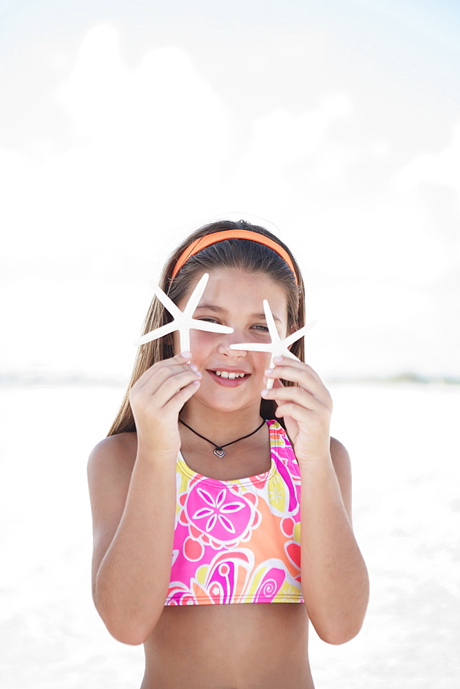 Girl on beach holding delicate starfish