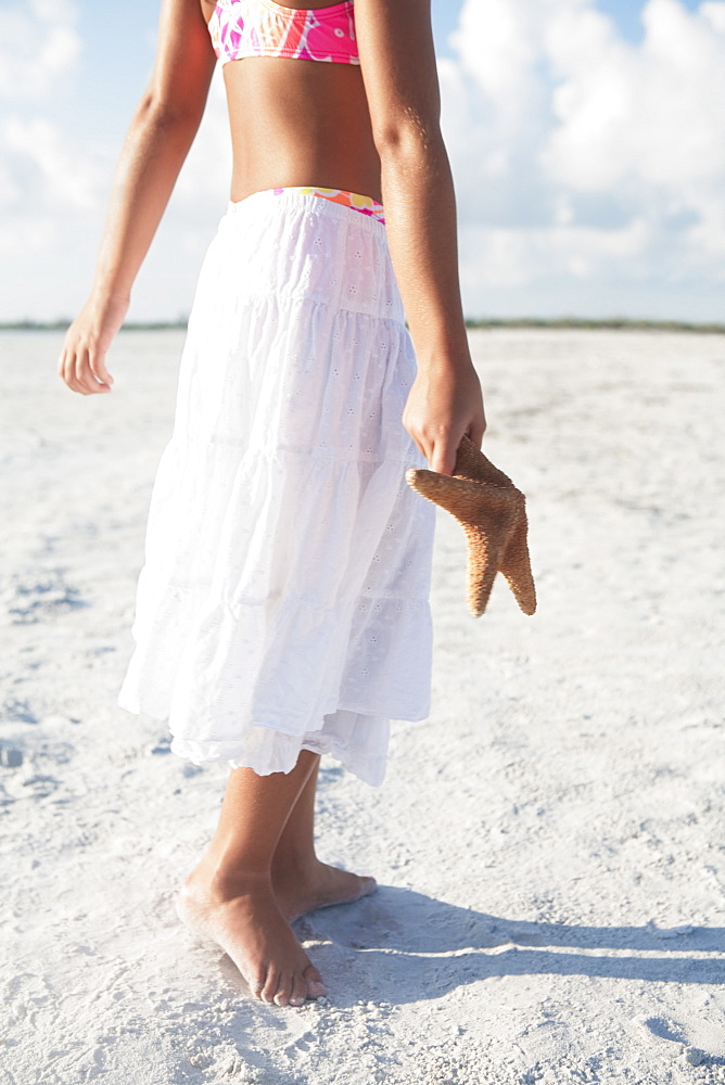 Girl walking with starfish on beach