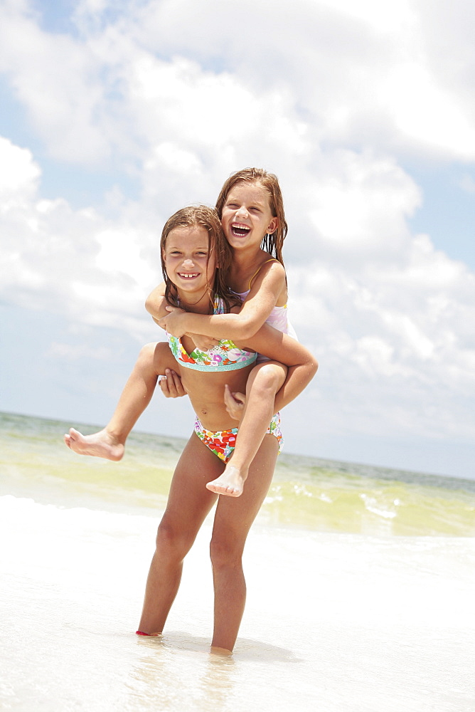 Girl carrying sister in ocean