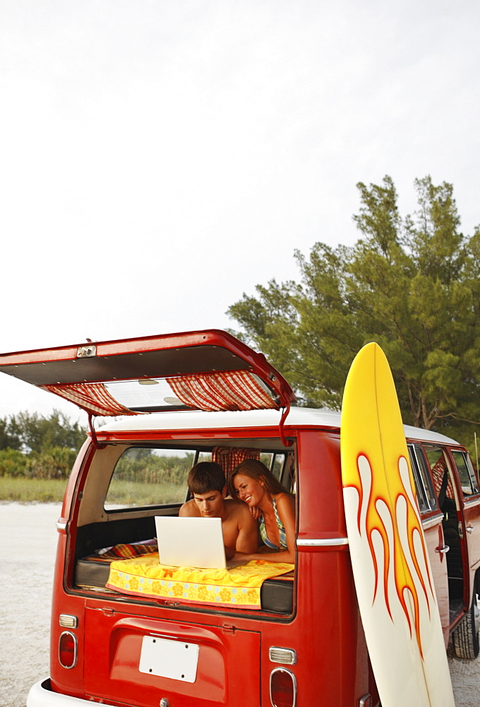 Young couple using laptop in van on beach