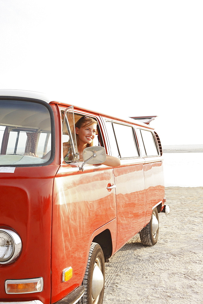 Teenage girl sitting in van on beach