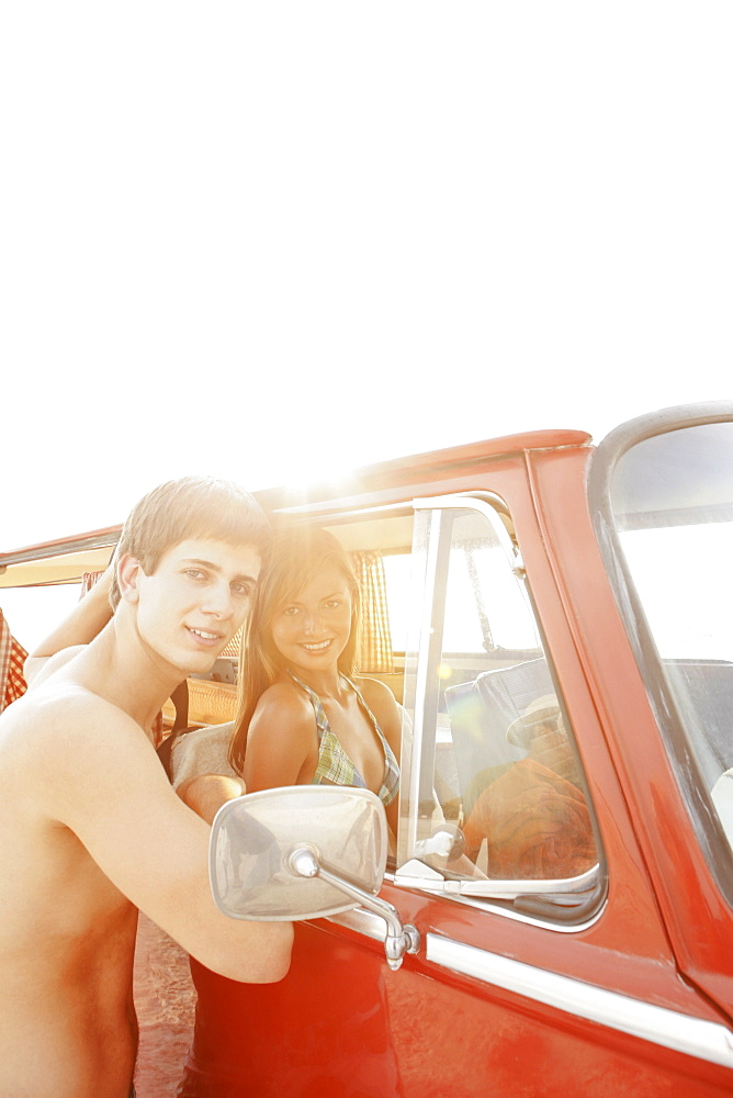 Teenage couple relaxing in van on beach