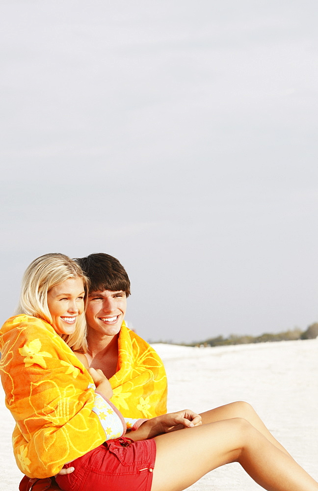 Young couple cuddling under towel on beach