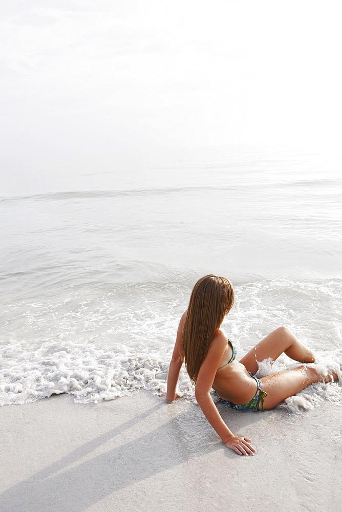 Teenage girl sitting in ocean