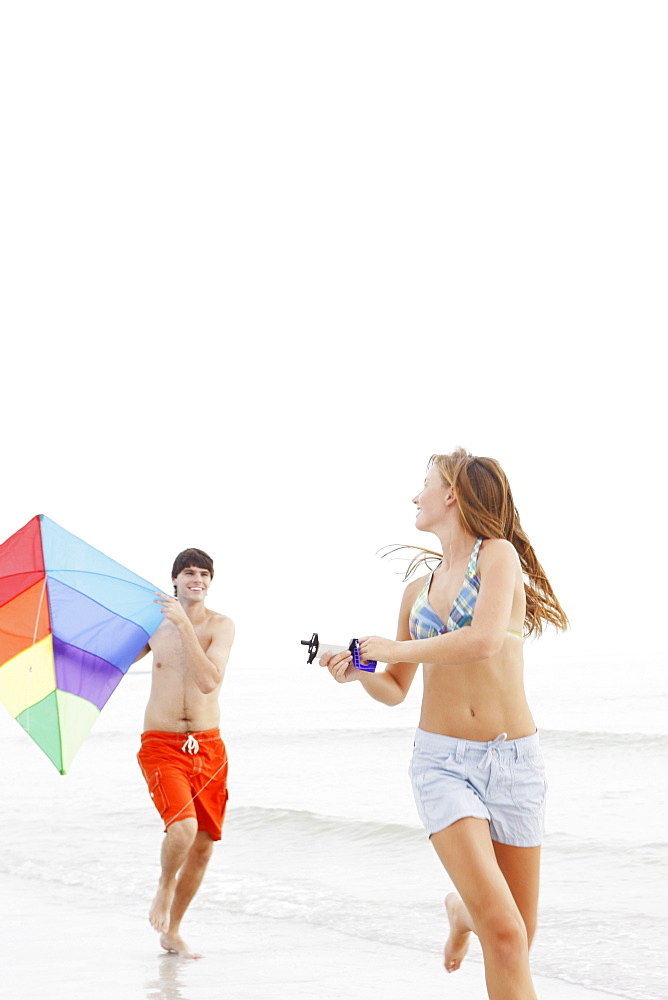 Friends flying kite on beach