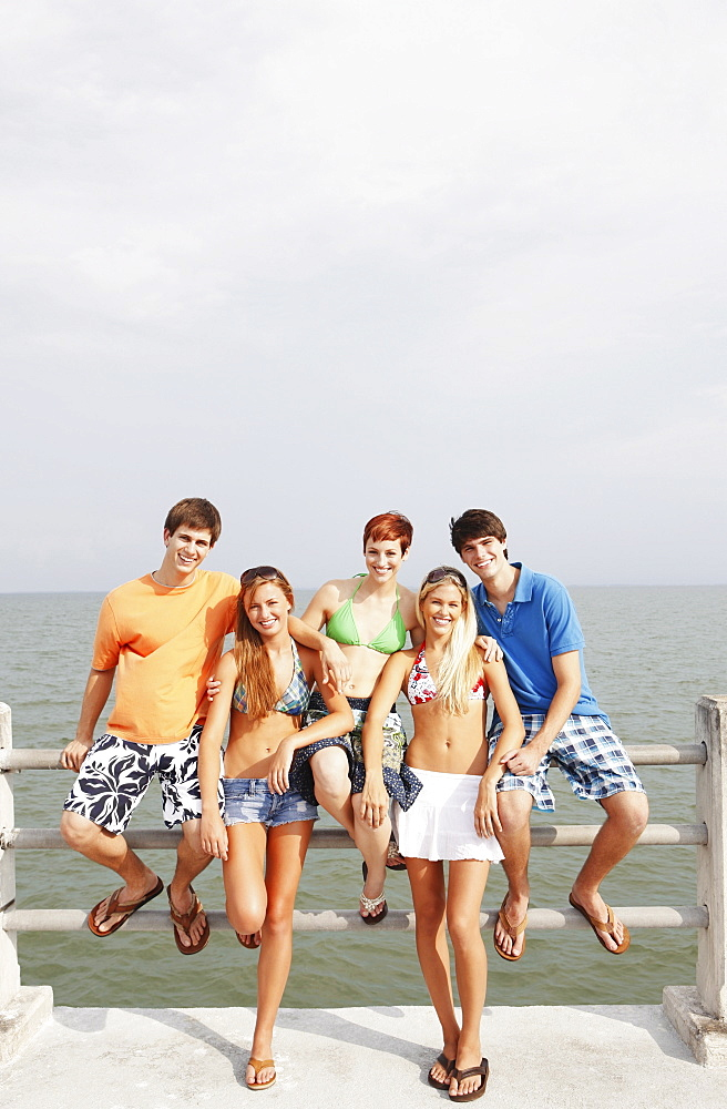 Friends posing on boardwalk railing