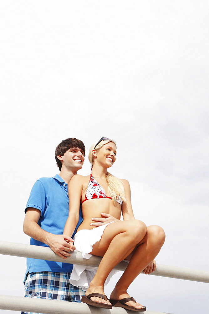Young couple hugging on boardwalk railing