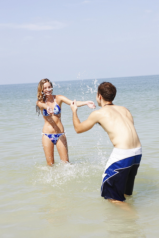 Teenage couple splashing each other in ocean