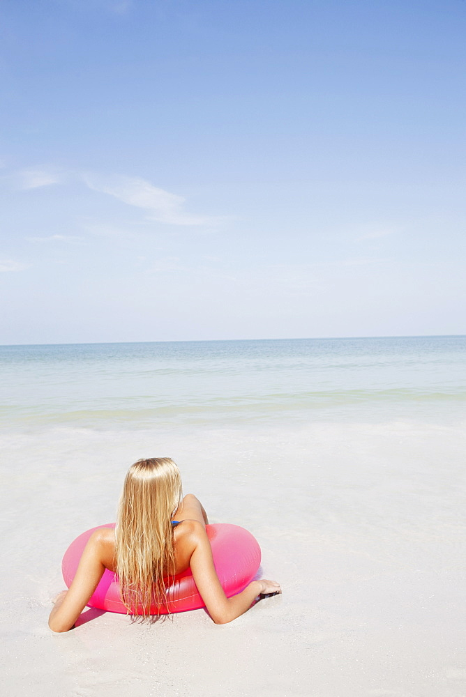Teenage girl sitting in inflatable ring in shallow ocean