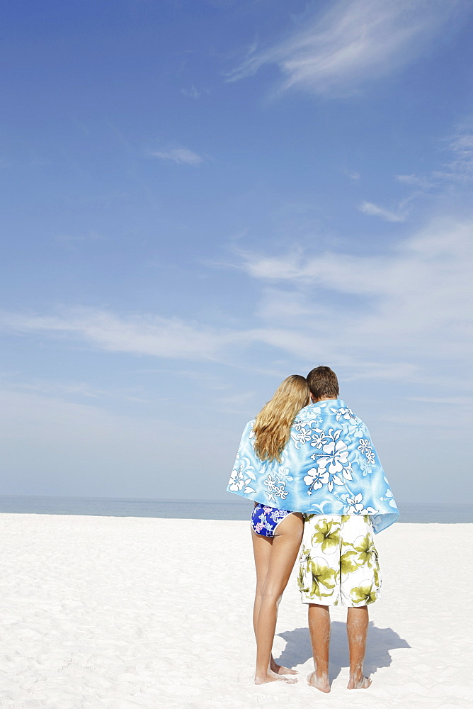 Teenage couple sharing towel on beach