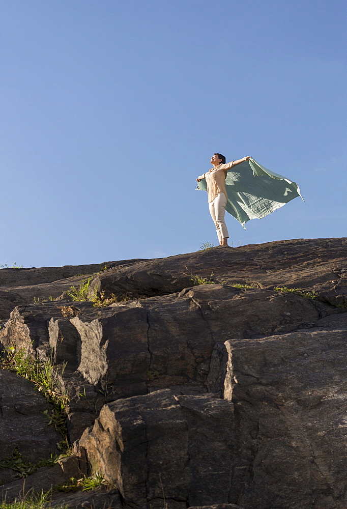 Mature woman standing on cliff with arms raised