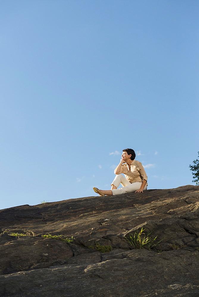 Mature woman sitting on rock