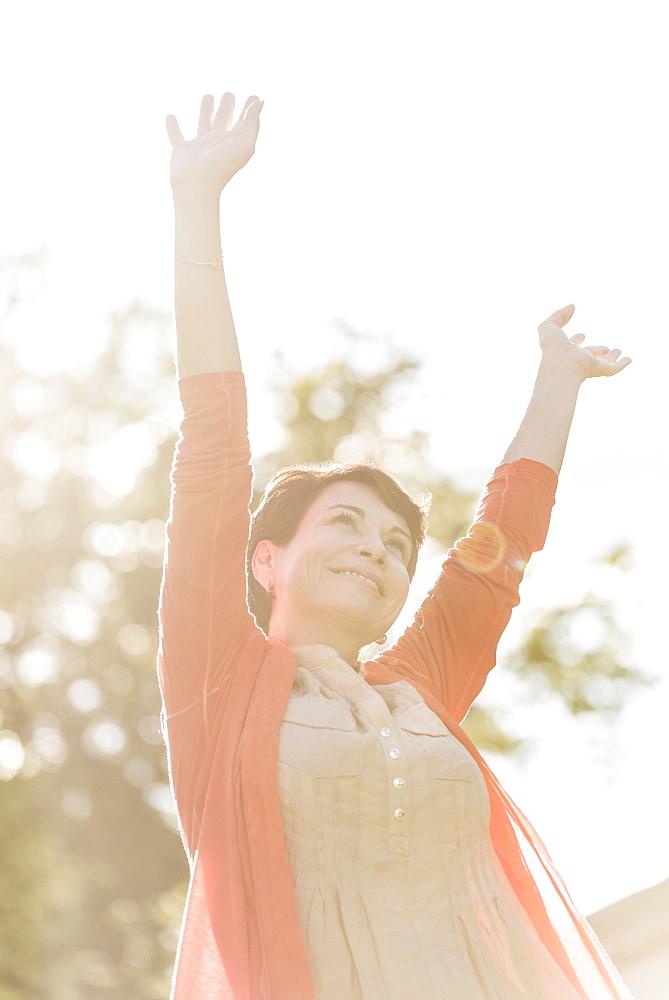 Mature woman raising hands in sunlight