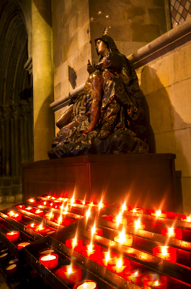 Candles in front of Virgin Mary statue in Monastery of Jeronimos, Lisbon, Portugal