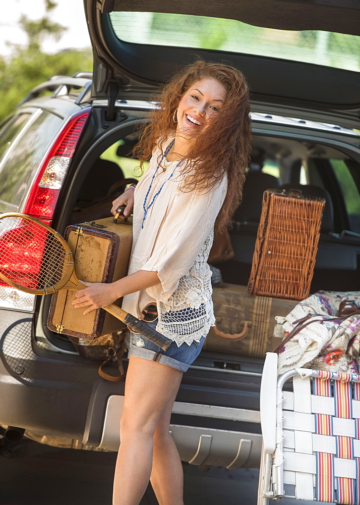 Portrait of young woman packing luggage into car