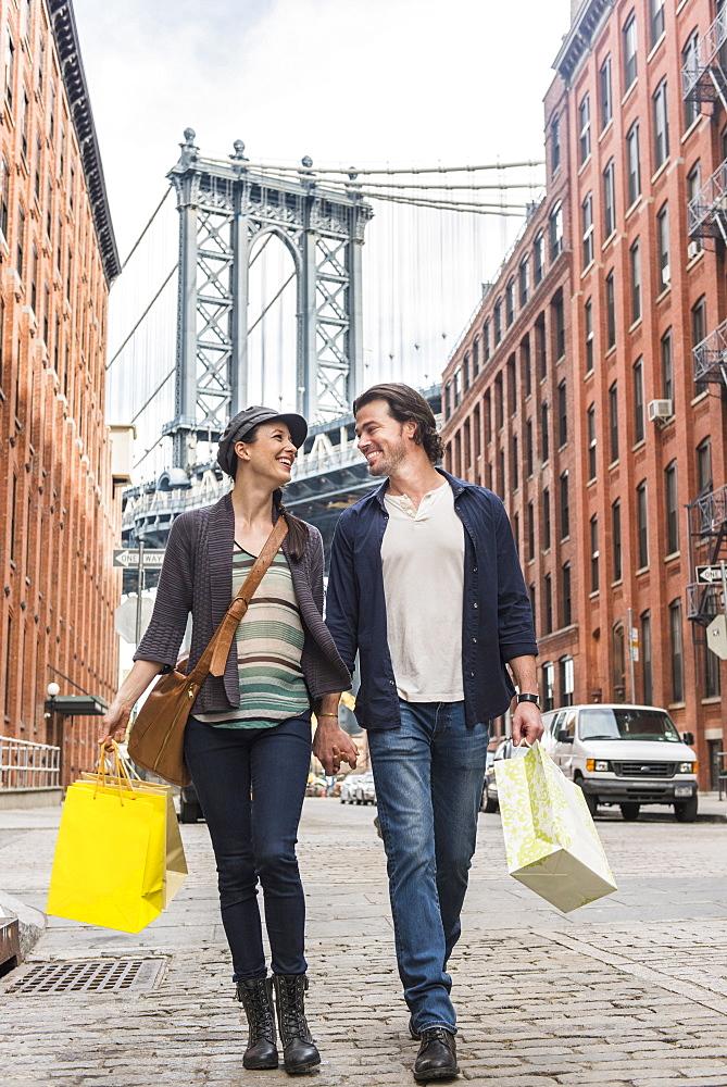 Couple walking on street, Brooklyn Bridge in background, Brooklyn, New York