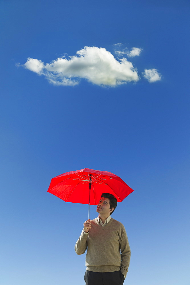 Man holding umbrella under cloud