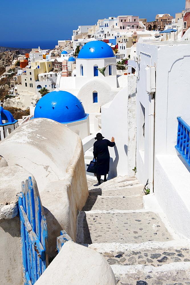 Greece, Cyclades Islands, Santorini, Oia, Woman descending steps past traditional buildings