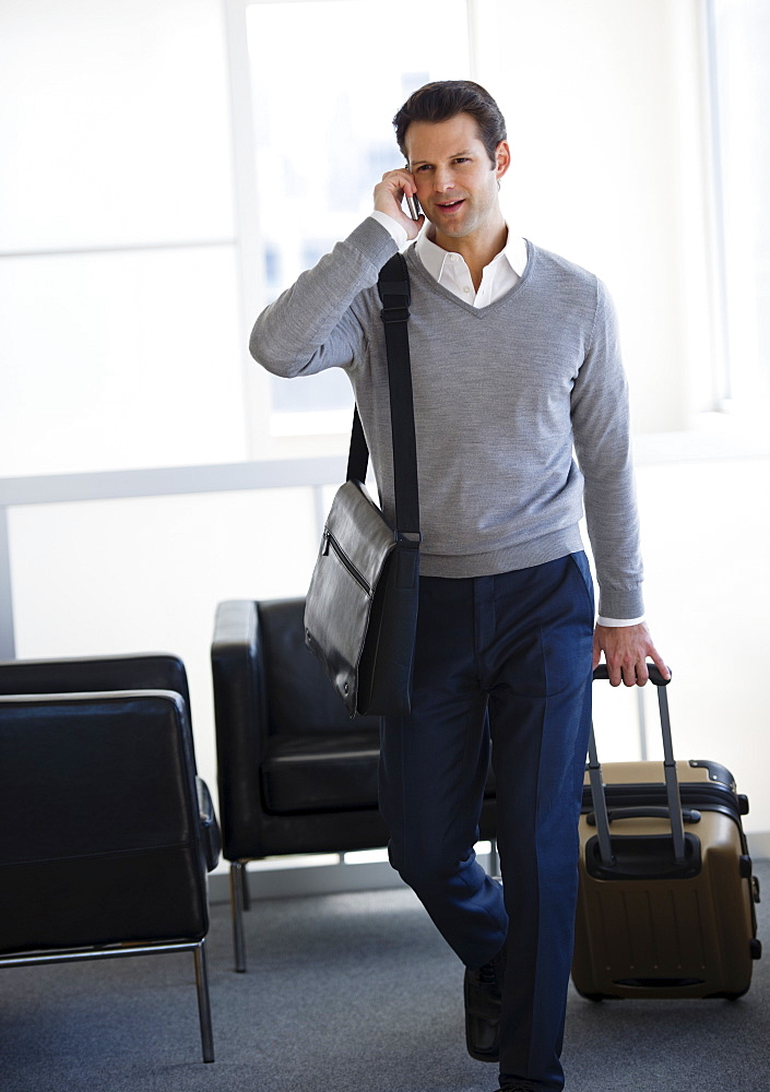Businessman pulling suitcase and talking on mobile phone in airport lounge