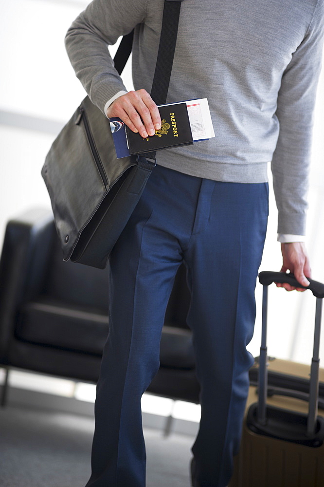 Businessman holding passport and suitcase