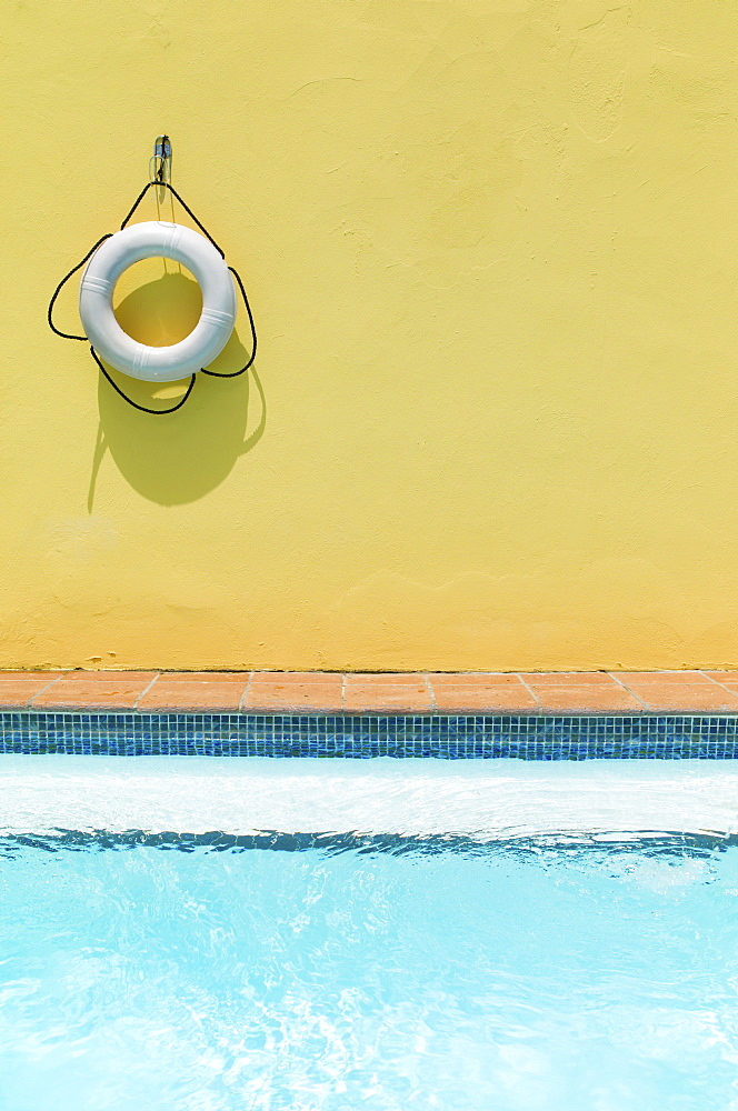 Lifebelt hanging on yellow wall by swimming pool