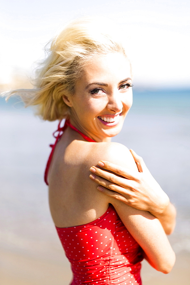 Portrait of woman wearing red swimming costume on beach