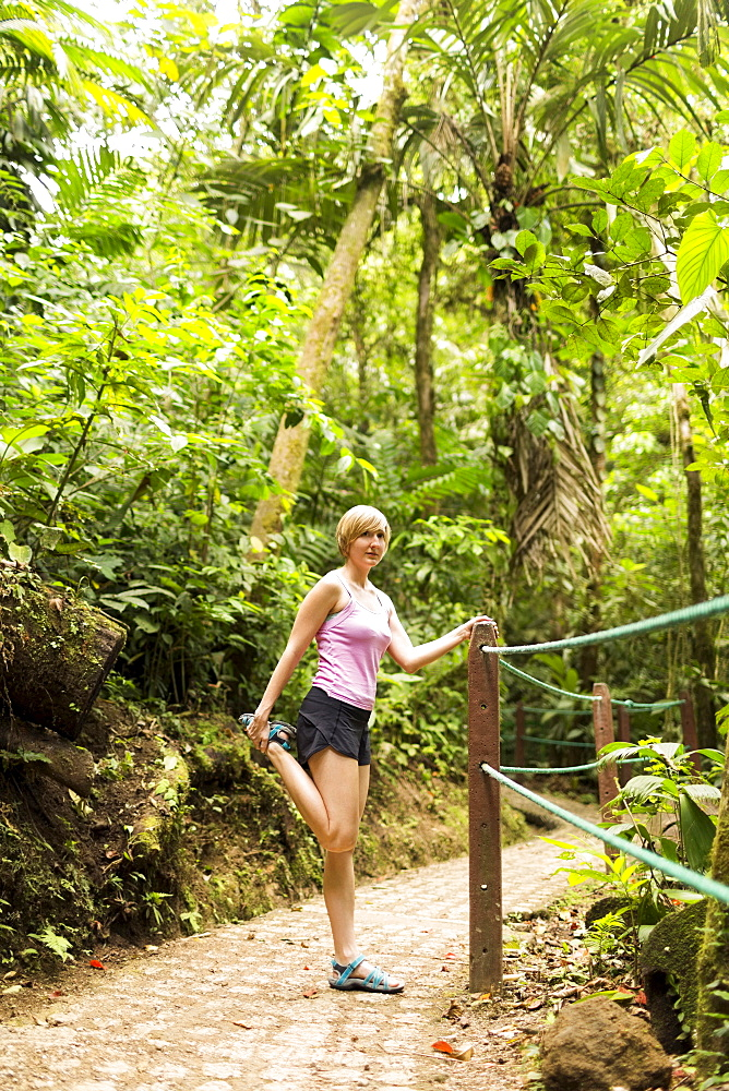 Woman in forest, stretching leg, Costa Rica