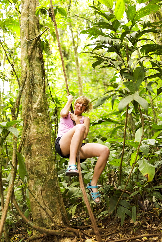 Woman swinging on rope in jungle, Costa Rica