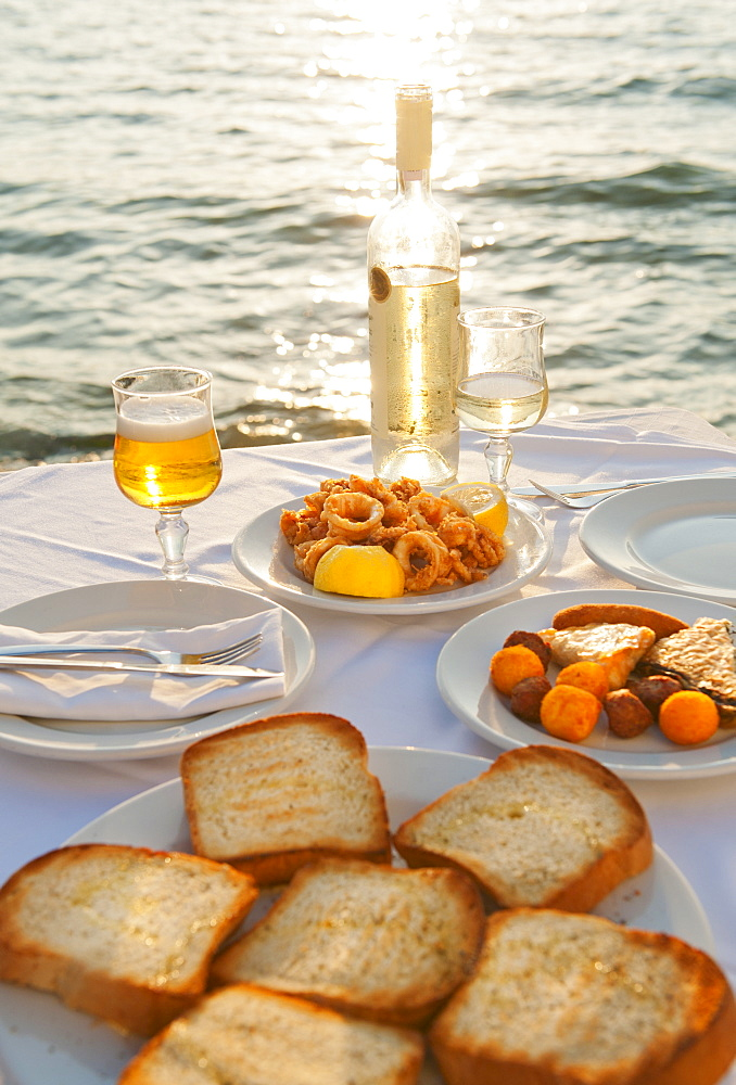 Greece, Cyclades Islands, Mykonos, Calamari appetizer on set table by sea