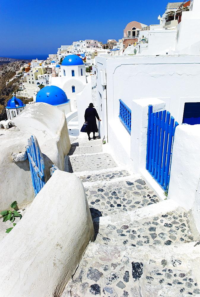 Greece, Cyclades Islands, Santorini, Oia, Woman walking down steps in town