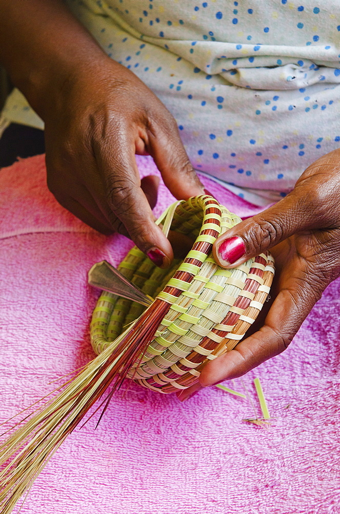 USA, South Carolina, Charleston, Close up of woman's hand weaving sweetgrass basket