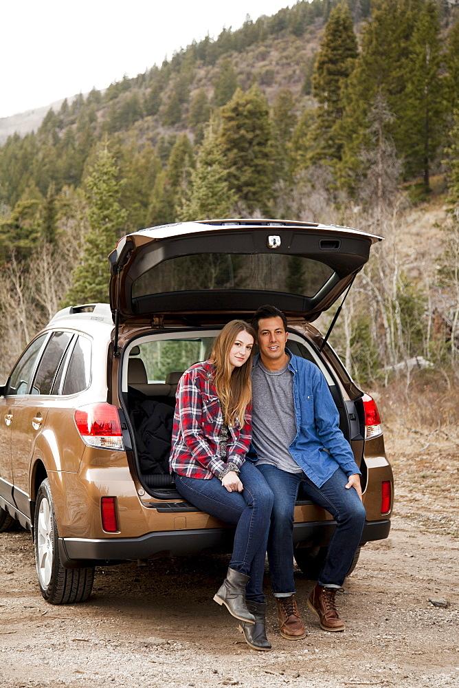 Portrait of young couple sitting in car trunk in non-urban scene, Salt Lake City, Utah