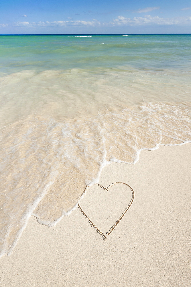 Heart drawing in sand on beach