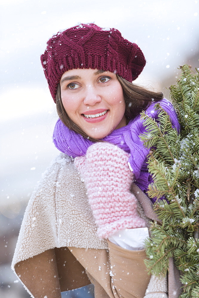 Portrait of young woman wearing knit hat, gloves and scarf an carrying fir wreath