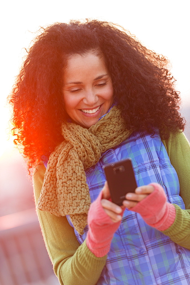 Portrait of mid adult woman using mobile phone at sunset