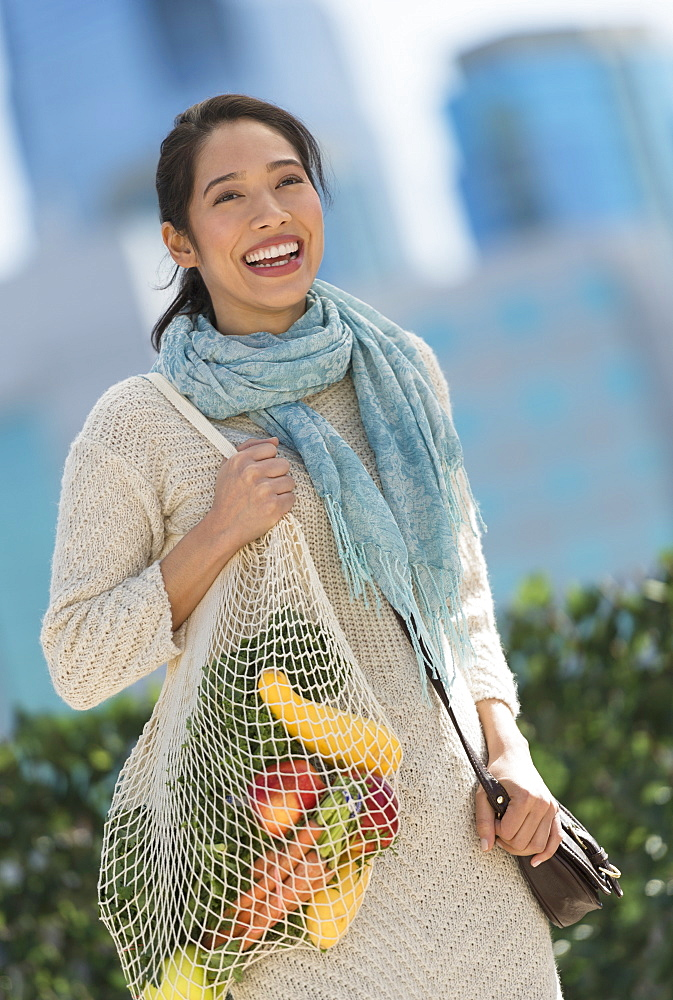 Portrait of smiling young woman with grocery shopping bag