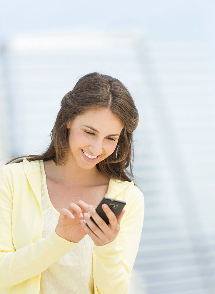 Young woman photographing herself with mobile phone