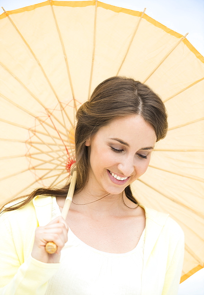 Portrait of beautiful young woman with parasol