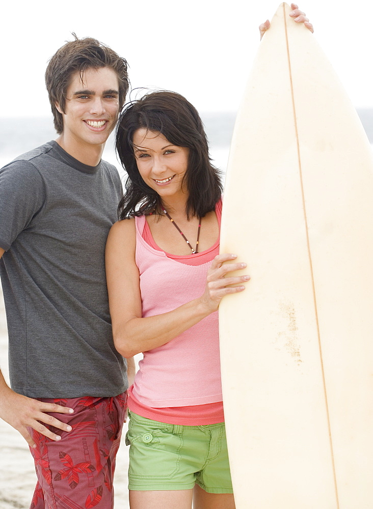 Couple holding surfboard and smiling