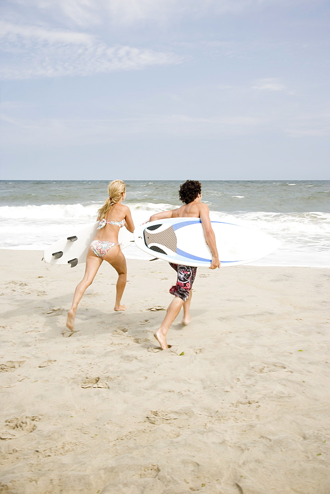 Couple running with surfboards