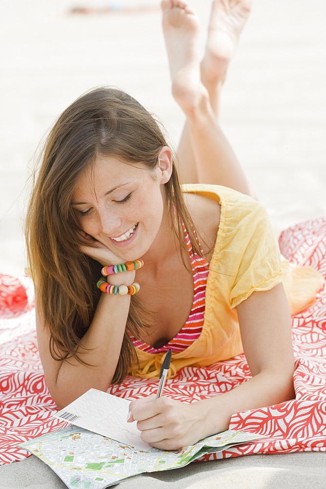 Women writing letter at beach