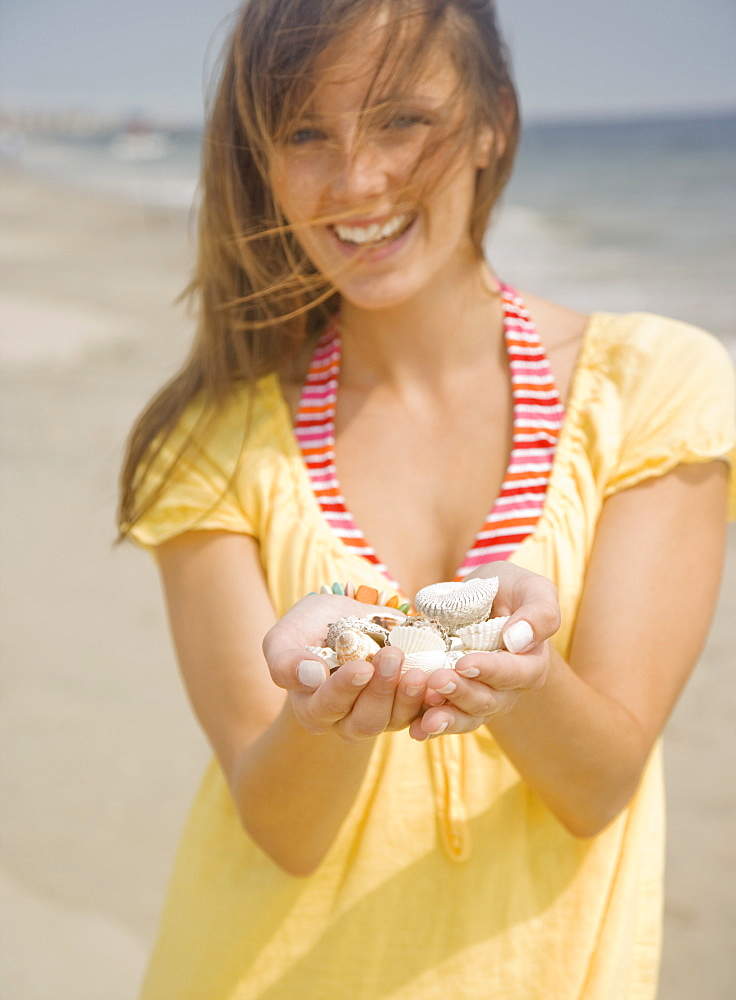 Woman holding handful of shells