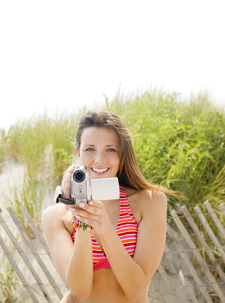 Woman holding video camera at beach