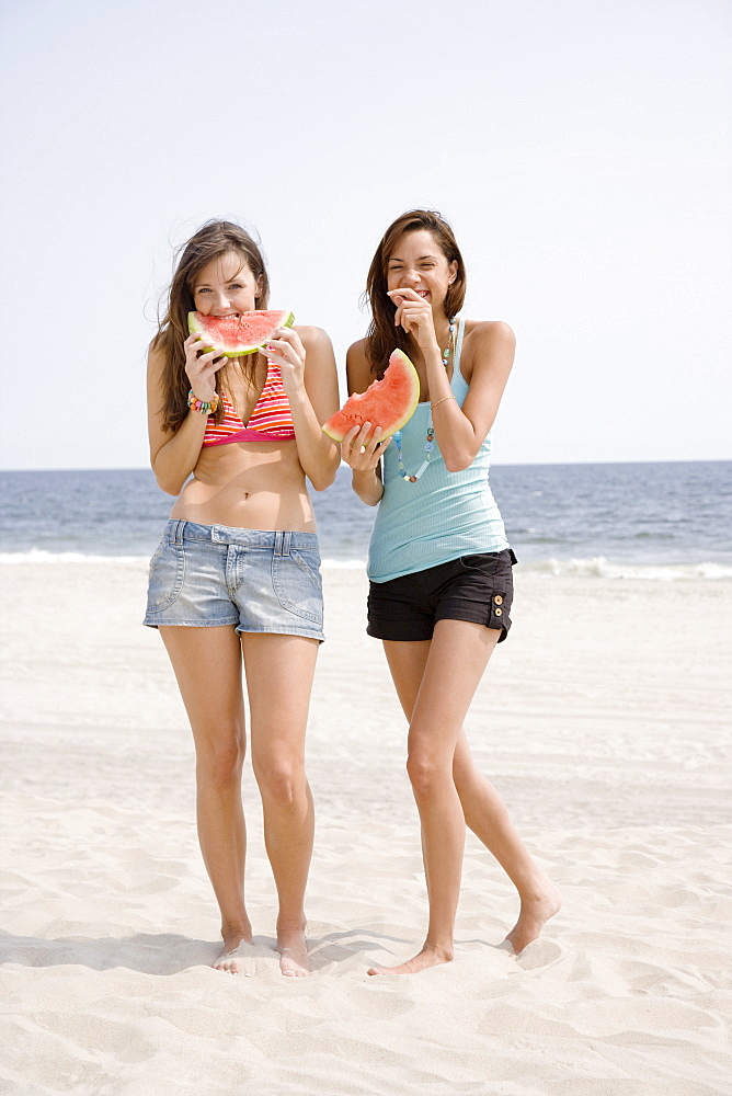 Women eating watermelon at beach
