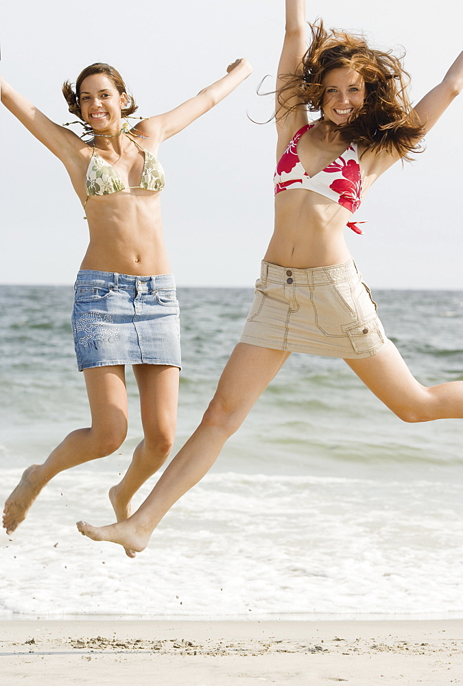 Young women jumping at beach