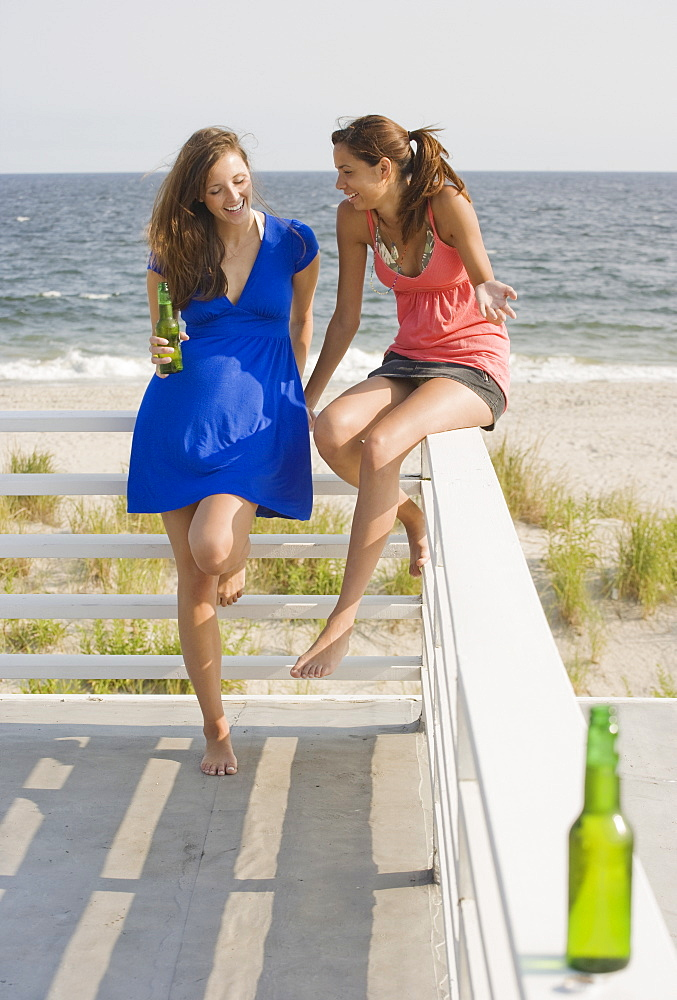 Two women leaning on railing at beach