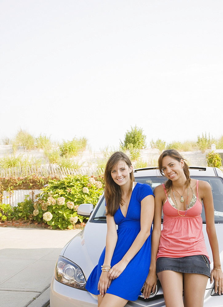 Young women sitting on car